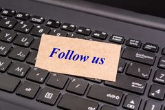 Follow us note. Laptop Keyboard and Follow us Card Note Royalty Free Stock Image