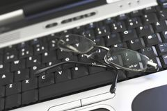 Laptop keyboard with glasses. Shallow focus on glasses royalty free stock image