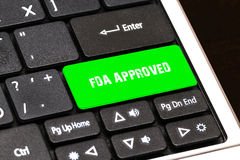 On the laptop keyboard the green button written FDA APPROVED Stock Photo