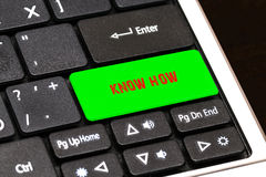 On the laptop keyboard the green button written KNOW HOW Stock Photo
