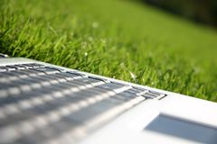 Laptop keyboard in a green field. Closeup of laptop keyboard in a clean green sports field Royalty Free Stock Photos