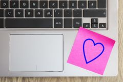 Laptop keyboard with heart note. Keyboard of a laptop with a red note written heart on wooden background Stock Images