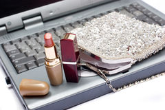 Laptop keyboard with lipsticks and silver  bag Stock Images