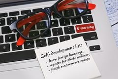 Onilne education and self development system concept. Laptop keyboard with nifty eyeglasses and a to do list on it. Enter key on keyboard replaced with a e Stock Photography