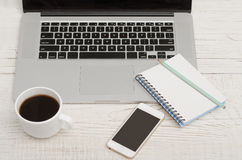 Laptop keyboard, notebook with a pencil, a smartphone and a mug of coffee, top view Royalty Free Stock Images