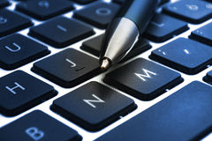 Laptop keyboard with pen closeup Stock Images