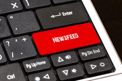 On the laptop keyboard the red button written Newsfeed Royalty Free Stock Image