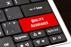 On the laptop keyboard the red button written Quality Assurance.  Royalty Free Stock Photo