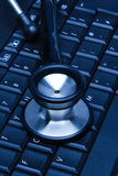 Laptop keyboard with stethoscope Royalty Free Stock Photo