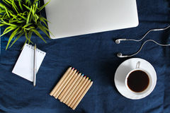 Laptop keyboard, white cup of tea on saucer, notepad, pen and green plant in the corner on dark blue crumpled jeans background. Royalty Free Stock Image