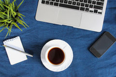 Laptop keyboard, white cup of tea on saucer, notepad, pen and green plant in the corner on dark blue crumpled jeans background. Stock Photography