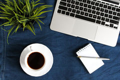Laptop keyboard, white cup of tea on saucer, notepad, pen and green plant in the corner on dark blue crumpled jeans background. Stock Photo