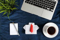 Laptop keyboard, white origami shirt with red tie near white cup of tea on saucer dark blue crumpled jeans background. Royalty Free Stock Image