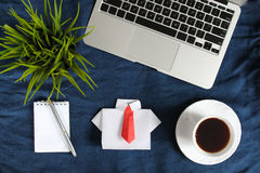 Laptop keyboard, white origami shirt with red tie near white cup of tea on saucer dark blue crumpled jeans background. Stock Image