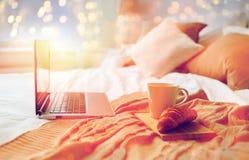 Laptop, koffie en croissant op bed bij comfortabel huis Stock Foto