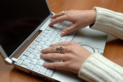 Laptop and ladies hands. Small laptop and ladies hands on the wood desktop Royalty Free Stock Photos
