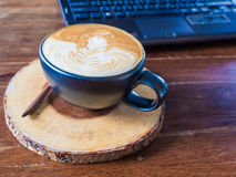 Laptop with latte art coffee cup on old wooden table Stock Photo