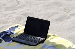 A laptop lays on towel in the beach. Daylight Stock Photo