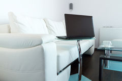 Laptop in living room. Modern living room with white leather sofa and laptop Stock Images