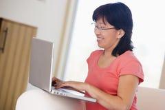 laptop living room smiling woman Στοκ Εικόνα