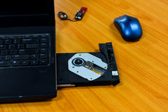 The laptop is loaded with a DVD drive on table background Stock Photos