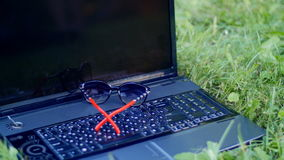 Laptop lying on the grass in the park - lay down glasses on laptop.  stock footage