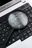 Laptop with a magnify glass. Close up Royalty Free Stock Image