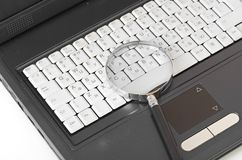 Laptop with a magnify glass Stock Images