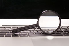 Laptop With Magnifying Glass Royalty Free Stock Photos