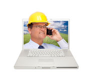 Laptop and Man with Hard Hat on Cell Phone Stock Photography