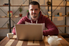 Laptop and man with hood Royalty Free Stock Photo