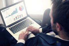 laptop man working Οικονομικά διαγράμματα στην οθόνη σημειωματάριων Στοκ φωτογραφία με δικαίωμα ελεύθερης χρήσης