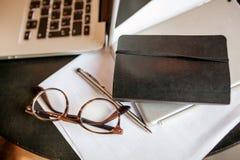 Laptop met blocnote en glazen op de lijst Stock Fotografie