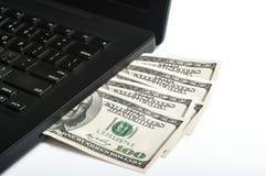 Laptop met geld die uit komen Stock Afbeeldingen