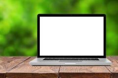 Laptop met het lege scherm op houten lijst aangaande groen Stock Afbeelding