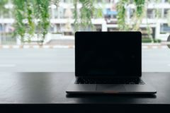 Laptop met het lege scherm op lijst, Conceptuele werkruimte, Laptop computer met het lege witte scherm op lijst, Groene achtergro stock fotografie