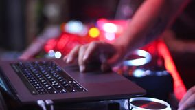 Laptop met het mengen van programma en van DJ mixerlichten in dark Deejay het aanpassen muziek bij de nachtpartij, controles stock videobeelden