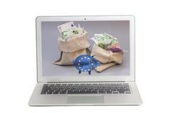 Laptop met Twee geldzak met euro en glasspaarvarken met Vlag van Europese Unie op het scherm stock foto