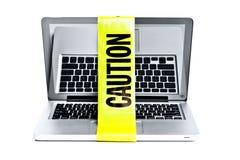 Laptop mit Achtungband um es Stockbilder