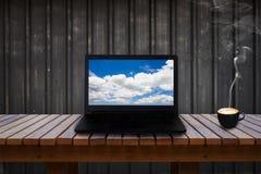 Laptop mit blauem Himmel und Wolke auf Schirm auf Holztisch und einem Tasse Kaffee Stockfotografie