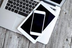 Laptop mit digitaler Tablette und Handy auf Holztisch Lizenzfreies Stockfoto