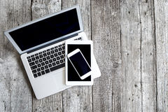 Laptop mit digitaler Tablette und Handy auf Holztisch stockbild