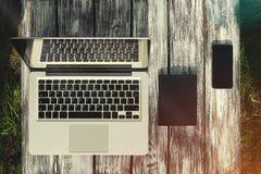 Laptop mit einem Notizbuch, einem Telefon und Kopfhörern auf einem Hintergrund von Brettern Lizenzfreies Stockbild