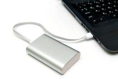 Laptop mit einem powerbank auf weißer Tabelle Lizenzfreie Stockfotos