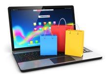 Laptop mit Gruppe Farbpapiereinkaufstaschen Stockfoto