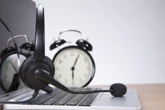 Laptop mit Kopfhörer und Wecker Stockfotos
