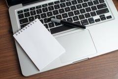 Laptop mit Notizblock und Stift lizenzfreie stockfotos