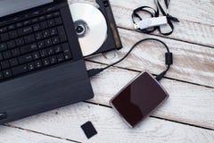 Laptop mit pendrive, Sd-Karte, CD und tragbarem Festplattenlaufwerk Lizenzfreie Stockfotografie