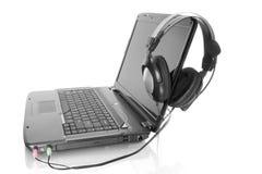 Laptop mit Stereokopfhörer Stockfotografie