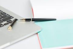Laptop mit Stift und Notizbuch Stockbilder